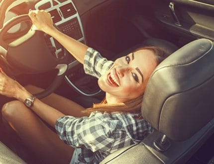Attractive young woman in a convertible car